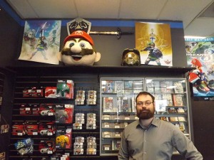 The branch manager of Game Changerz, Michael Morrissey, poses by some of his incredible videogame items.