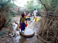 Refugees at Kakuma Camp gather water after flooding.