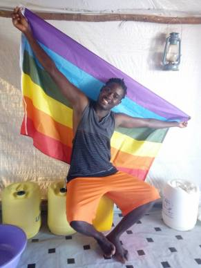Mbazira Moses, who provided the following photos, poses with the LGBT flag.