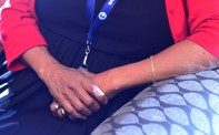 Halima's sure hands are lightly adorned with gold jewelry.